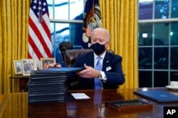 FILE - President Joe Biden signs his first executive orders, including halting work on a border wall, in the Oval Office of the White House in Washington, Jan. 20, 2021.