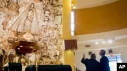 """Presiden Barack Obama belajar tentang gereja """"Shrine of Our Lady of Charity"""" dari Pastor Juan Rumin Dominguez dalam kunjungan mendadak di Miami (28/5). (AP/Pablo Martinez Monsivais)"""