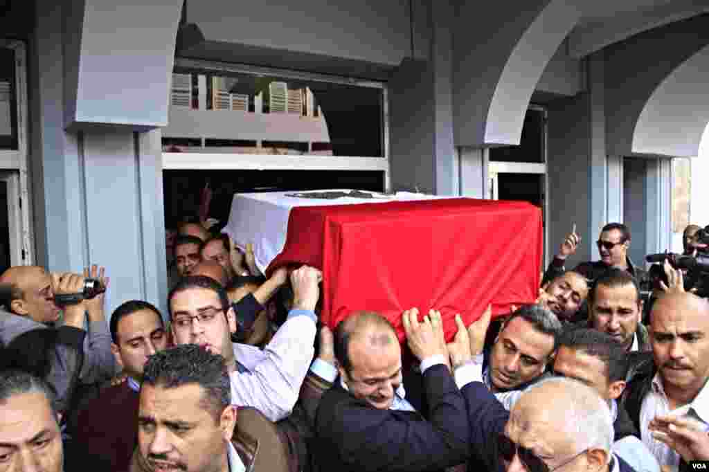 The body of slain Police Brigadier General Tariq al-Mirjawi is carried out of the Agouza Police Hospital after a series of explosions hit Cairo University, Cairo, Egypt, April 2, 2012. (Hamada Elrasam for VOA)
