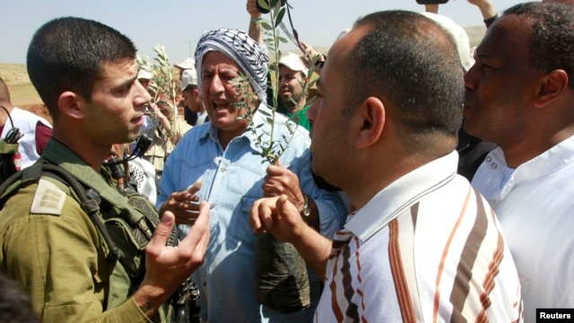 Palestinian farmers argue with an Israeli soldier as they try to plant olive trees during a protest against what they say is land confiscation for Jewish settlements in the Jordan Valley, a hotly contested part of the occupied West Bank, April 8, 2014.