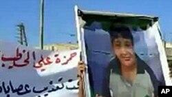 敘利亞一名示威者高舉一名在軍方鎮壓示威活動期間遭殺害的女童照片
