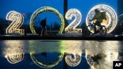 """La gente pasa junto a los números """"2020"""" instalados para celebrar la próxima Navidad y Año Nuevo en Moscú, Rusia."""