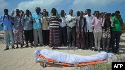 FILE - Relatives and fellow journalists pray as they stand next to the body of Somali journalist Abdulaziz Ali Haji during his funeral, Sept. 28, 2016, in Mogadishu.