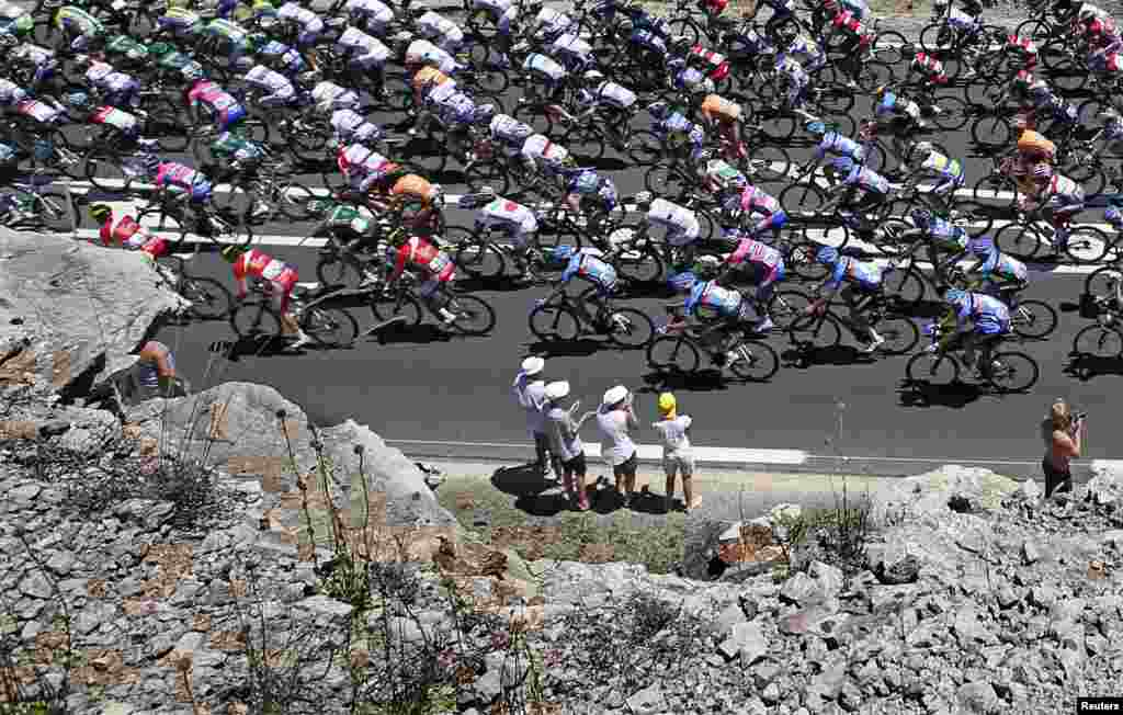 Fans watch as a pack of riders cycles past during the 205.5 km seventh stage of the centenary Tour de France from Montpellier to Albi.