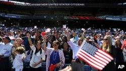 Orang-orang bersorak setelah mengucapkan janji setia dalam upacara naturalisasi bagi 755 warga negara AS yang baru di Turner Field, Atlanta (16/9). (AP/David Goldman)