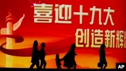 北京居民走过迎接中共十九大召开的大型电子屏幕。(2017年10月15日)