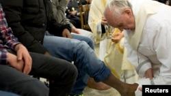 "Paus Fransiskus membasuh kaki seorang napi di penjara remaja ""Casal del Marmo"" di Roma (28/3) dalam rangkaian upacara Kamis Putih."