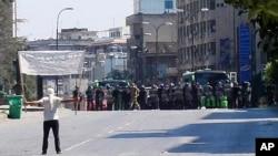 A protester faces riot police at Khalidia, near Homs, Syria November 4, 2011.