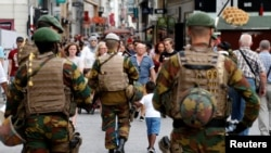 Belgian soldiers patrol on a square after a man was seen wearing a thick coat with wires protruding from underneath in central Brussels, July 20, 2016.