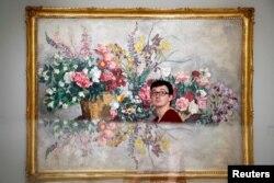 미술관에 전시된 유럽 인상파 화가 작품 표면에 관람객 얼굴이 비치고 있다.