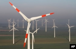 FILE - Wind turbines produce green energy in Nauen near Berlin, Germany, Oct. 12, 2012.