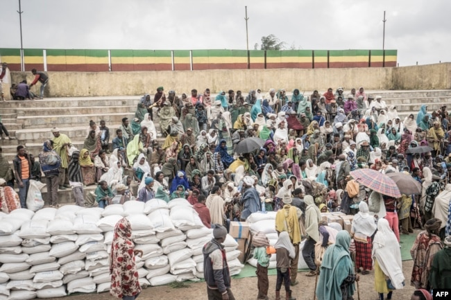 People who fled the war from May Tsemre, Addi Arkay and Zarima gather around in a temporarily built internally displaced people (IDP) camp to receive their first bags of wheat from the World Food Program in Debark, 90 kilometers of the city of Gondar, Ethiopia, Sept. 15, 2021.
