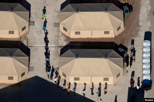 Immigrant children are led by staff in single file between tents at a detention facility next to the Mexican border in Tornillo, Texas, June 18, 2018.