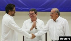 FILE - Lead FARC negotiator Ivan Marquez, left, and lead Colombian government negotiator Humberto de la Calle shake hands while Cuba's Foreign Minister Bruno Rodriguez looks on after the signing of a final peace deal in Havana, Cuba, Aug. 24, 2016.