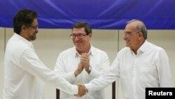 Глава делегации ФАРК, Иван Маркес, (слева) и представитель Колумбийского правительства Умберто де ла Калле пожимают руки после подписания мирного соглашения. Гавана, Куба, 24 августа 2016.