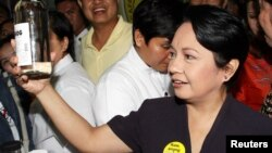 Mantan presiden Filipina Gloria Macapagal Arroyo memegang botol berisi lambanog, anggur lokal dari kelapa, di Manila. (Foto: Dok)