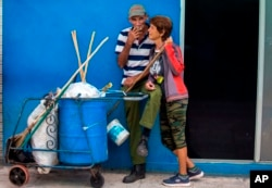 In this April 3, 2018 photo, street cleaners take a break as they work on the main boulevard in Holguin, Cuba.