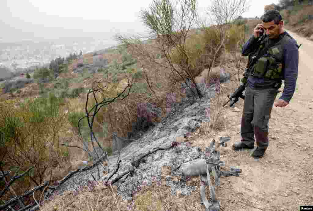 An Israeli security coordinator stands next to the remains of a rocket after it landed near the northern town of Kiryat Shmona, Israel, Dec. 29, 2013.