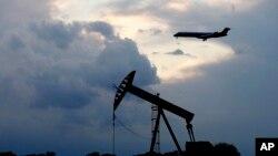21일 미국 오클라호마주 오클라호마시티에 해가 지는 가운데 석유를 뽑아 올리는 '펌프잭' 위로 항공기가 착륙하고 있다. 신종 코로나바이러스 감염증(COVID-19)의 여파로 항공편 결항과 공장 가동 중단 등 원유 수요가 줄어들면서 유가가 계속 하락하고 있다.