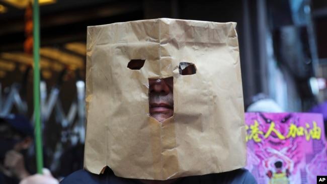 Un manifestante utiliza una bolsa de papel para cubrirse el rostro durante una marcha en Hong Kong, el domingo 6 de octubre de 2019. (AP Foto/Kin Cheung)