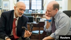 FILE - Former Cuba detainee Alan Gross, left — shown visiting with U.S. Senator Chris Coons of Delaware after his release, on Capitol Hill in Washington, Jan. 13, 2015.