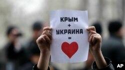 Một người Tatar Ukraina giơ tấm poster với dòng chữ 'Crimea + Ukraina = Trái tim' trong một cuộc biểu tình phản đối trước toà nhà chính phủ ở Simferopol, Crimea, Ukraina, 26/2/2014