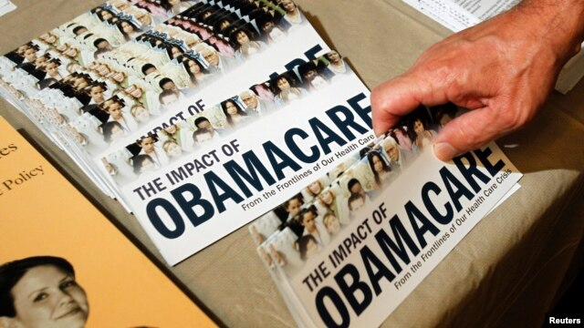 "A Tea Party member reaches for a pamphlet titled ""The Impact of Obamacare,"" at a ""Food for Free Minds Tea Party Rally"" in Littleton, New Hampshire in this October 27, 2012 file photo."