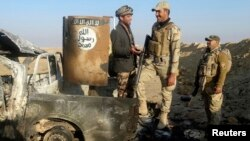 Iraqi security forces stand on a destroyed vehicle belonging to Islamic State militants on the outskirt of Ramadi, Dec. 21, 2014.