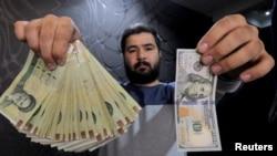 지난 1월 이란 테헤란의 경제지구에서 환전소 직원이 미국 100달러 지폐(오른쪽)와 이에 상응하는 이란 리알 지폐를 들고 있다.