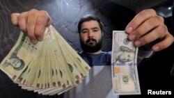 Pegawai tempat pertukaran uang memperlihatkan perbandingan nilai rial Iran dan dolar AS di Teheran, Iran, Januari 2016. (Reuters/Raheb Homavandi/TIMA)