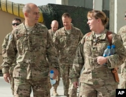 In this image provided by the U.S. Air Force, Lt. Gen. Jeffrey Harrigian, who is currently head of U.S. Air Force's operations throughout the region, walks with Lt. Col. Joy Boston, 455th Expeditionary Operations Support Squadron commander at Bagram Airfi
