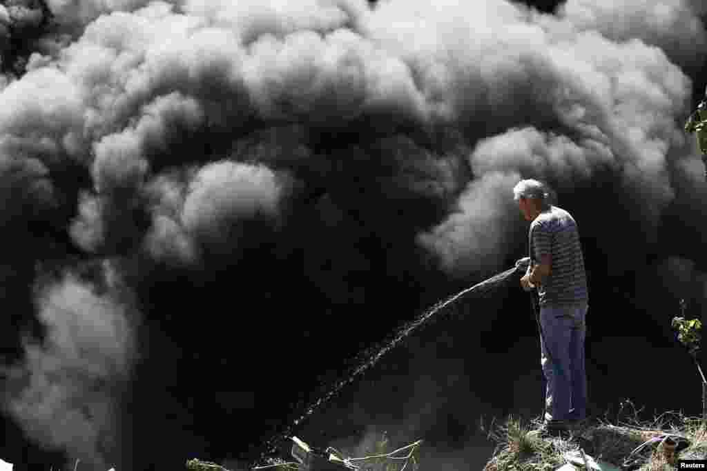 Homem tentando apagar incêndio numa lixeira ilegal em São José na Costa Rica, depois dos residentes terem decidido pegar fogo para tentar acabar com os mosquitos portadores do vírus Zica.