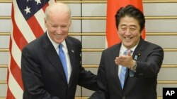 PM Jepang Shinzo Abe (kanan) menyambut Wapres AS Joe Biden sebelum pembicaraan di Tokyo, Selasa (3/12).