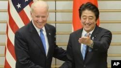 Wapres AS Joe Biden (kiri) dan PM Jepang Shinzo Abe berjabat tangan sebelum pertemuan mereka di Tokyo, Selasa (3/12).