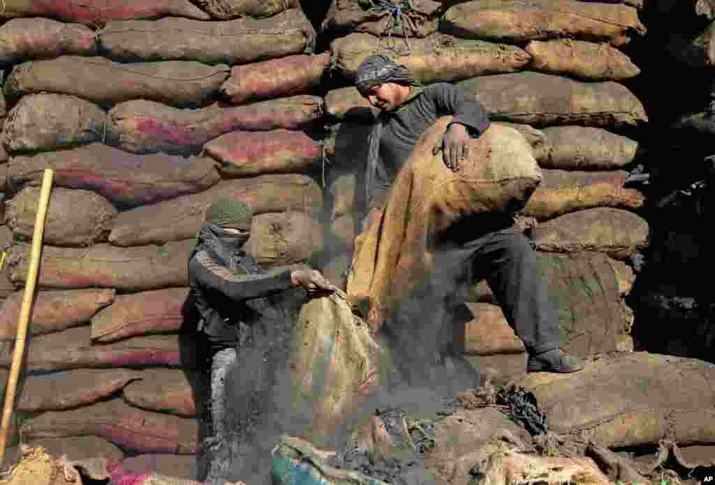 Afghan labors work at a charcoal shop on the outskirts of Kabul.