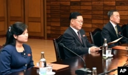 In this photo provided by South Korea Unification Ministry, the head of North Korean delegation Kwon Hyok Bong, center, and Hyon Song Wol, head of the Moranbong Band, left, sit during a meeting with South Korean officials at the North side of Panmunjom, N