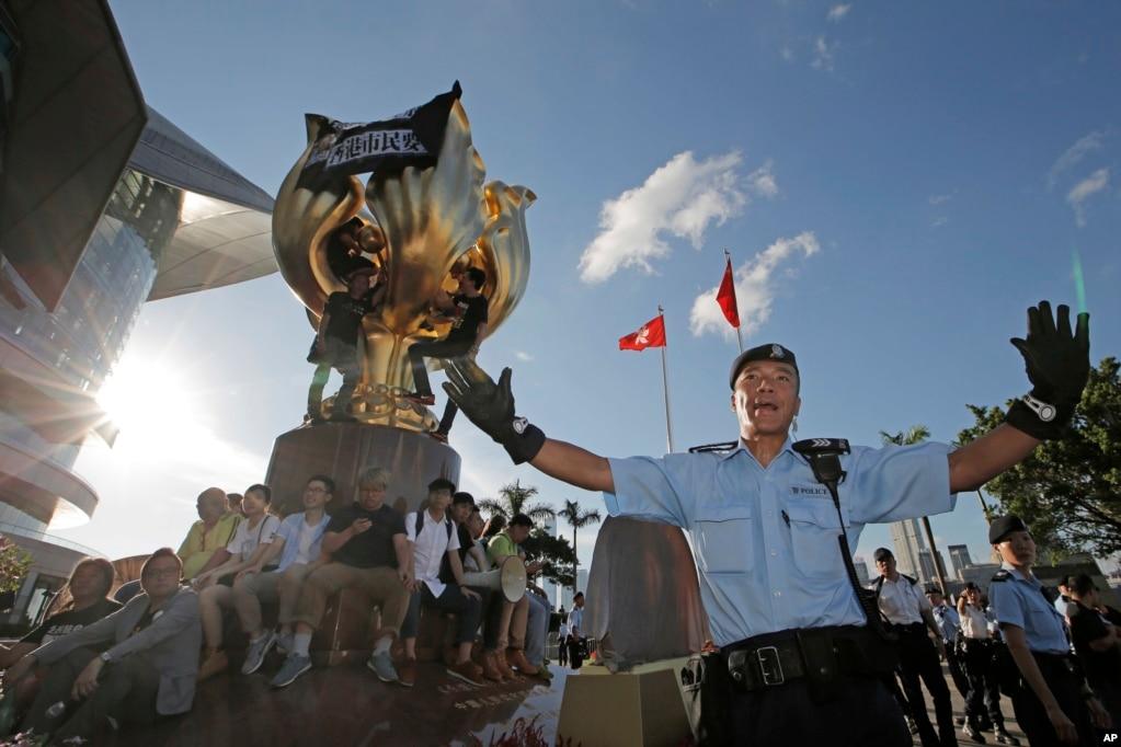 """在香港湾仔金紫荆广场( Golden Bauhinia Square),警察阻止抗议者爬上金紫荆雕塑。雕塑上已经有不少人,雕塑顶部挂着黑布,写着标语""""无条件释放刘晓波""""和""""香港市民要真普选""""(2017年6月28日)。这座大型雕塑是1997年香港回归中国时北京送的礼物。"""