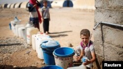 FILE - A displaced Iraqi boy fills a bottle with water in Jada camp south of Mosul, Iraq Aug. 9, 2017.