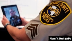 In this Friday, Aug. 13, 2021, photo Sheriff's Police Sgt. Bonnie Busching tests a video meeting with a personal electronic device at the Cook County Sheriff's Office in Chicago. (AP Photo/Nam Y. Huh)