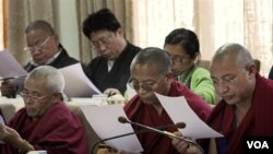Para anggota parlemen Tibet membaca pesan tertulis dari Dalai Lama dalam sesi parlemen di Dharmsala, Senin (14/3).