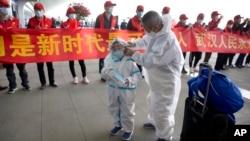 武汉解封,天河国际机场的旅客站在庆祝的标语横幅旁。(2020年4月8日)