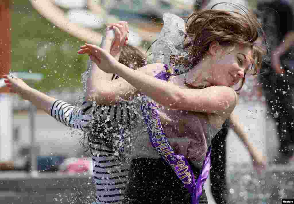 Secondary school graduates play in a fountain as they celebrate the last day of school, traditionally called the 'last bell' in central Kyiv, Ukraine.