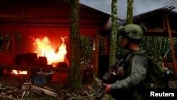 Un policía antinarcóticos colombiano resguarda un laboratorio de cocaína quemado, que según la policía pertenece a bandas criminales, en una zona rural de Colombia, el 2 de agosto de 2016.
