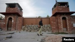 FILE - A police officer walks past Central Jail in Peshawar, June 21, 2012.
