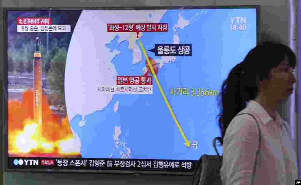 """2017年8月10日,在韩国首尔火车站,一名妇女走过电视屏幕,屏幕显示新闻报道朝鲜威胁袭击关岛,左上角的标志读为""""北韩宣布计划向关岛发射弹道导弹""""。朝鲜战略火箭部队的司令8月10日对朝鲜官媒朝中社表示,平壤将在八月中旬拟定一项向关岛发射四枚中程导弹的计划。关岛有大量美军驻扎。"""