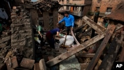 FILE - In this April 27, 2015 file photo a Nepalese family collects belongings from their home destroyed in Saturday's earthquake, in Bhaktapur on the outskirts of Kathmandu, Nepal. Last year saw the lowest financial costs from natural disasters worldwide since 2009 as the El Nino weather phenomenon reduced hurricane activity in the North Atlantic, a leading insurer said, Jan. 4, 2016.