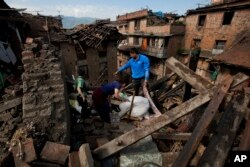FILE - In this April 27, 2015 file photo a Nepalese family collects belongings from their home destroyed in an earthquake, in Bhaktapur on the outskirts of Kathmandu, Nepal.