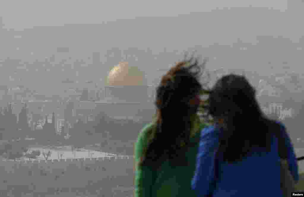 The Dome of the Rock is seen in the background as women look at the view from the Mount of Olives in Jerusalem during a dust storm.  Strong winds blowing clouds of dust grounded President Obama's helicopter, forcing him to make the short journey from Jerusalem to Bethlehem by motorcade.