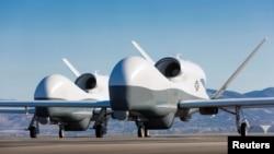 ເຮືອບິນບໍ່ທີບໍ່ມີຄົນຂັບສອງລຳ Northrop Grumman MQ-4C Triton ຈອດຢູ່ເດີ່ນ ບ່ອນທົດສອບ ຂອງບໍລິສັດ Northrop Grumman ທີ່ເມືອງພາມເດລ ລັດຄາລີຟໍເນຍ ວັນທີ 22 ພຶດສະພາ 2013.