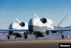 """2013年5月22日加利福尼亚州帕姆代尔市诺斯洛普·格鲁门公司测试设施停机坪上的两架RQ-4""""全球鹰""""型无人机"""